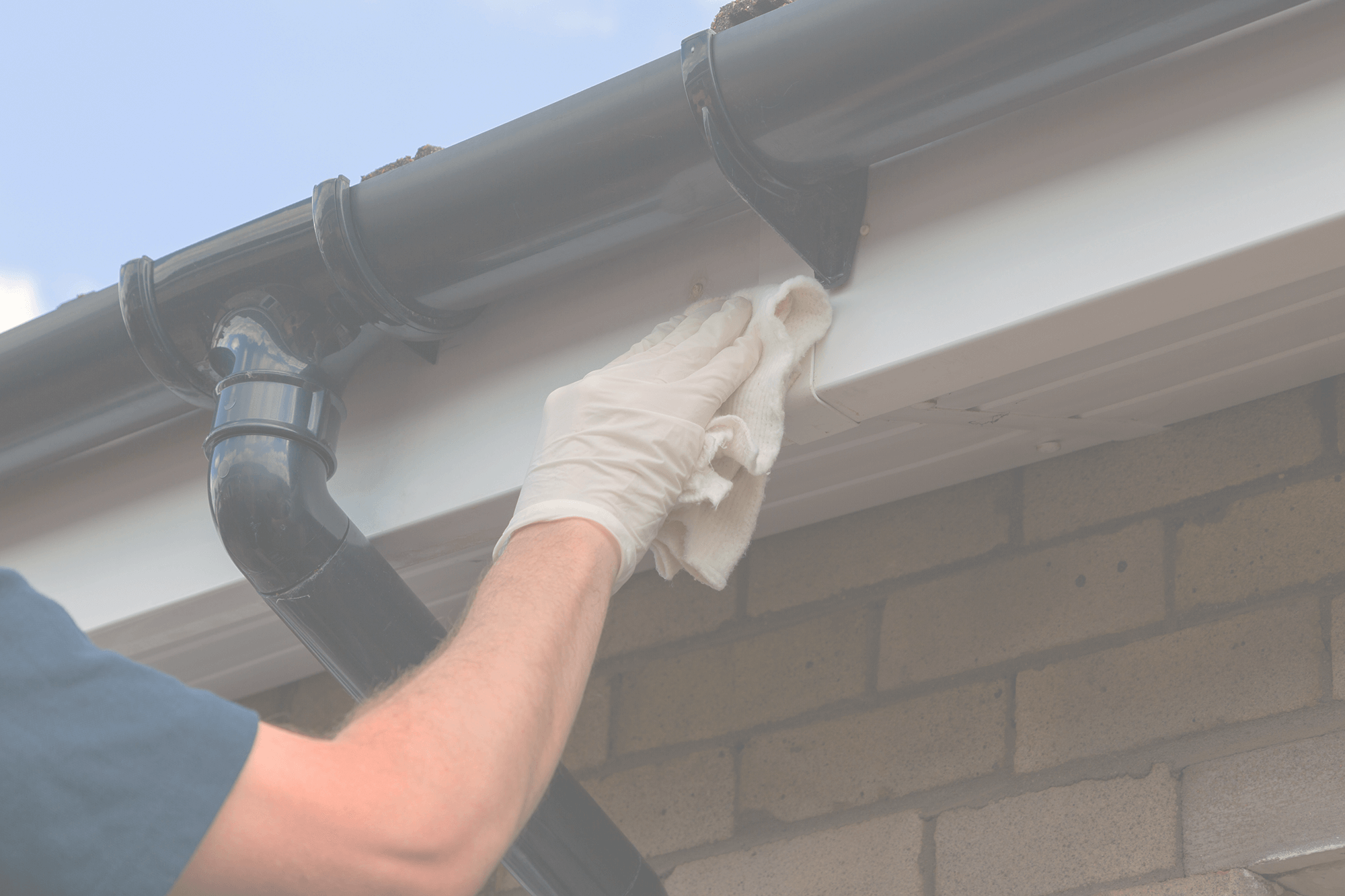 Close-up of an employee cleaning a gutter